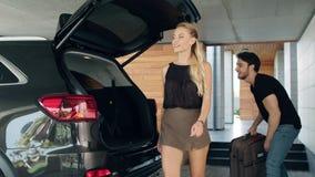 Bagagli di carico delle belle coppie in automobile al garage Bagaglio d'imballaggio della famiglia felice archivi video