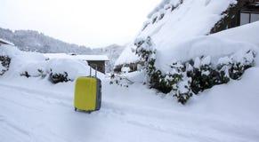 Bagagli gialli sulla strada con neve come fondo fotografie stock