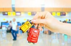 Bagaglio miniatura in mani femminili su fondo vago con i contatori di registrazione dell'aeroporto immagini stock