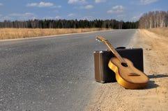 Bagaje y guitarra en el camino vacío Imágenes de archivo libres de regalías