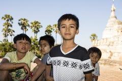 Bagan,缅甸, 2017年12月29日:三个男孩和女孩在Bagan骄傲地摆在 库存照片