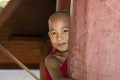 Bagan,缅甸, 2017年12月29日:年轻佛教新手在一根红色柱子后看恶作剧地 免版税库存照片