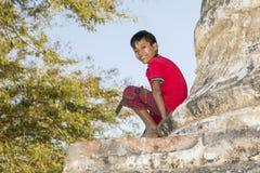 Bagan,缅甸, 2017年12月29日:有田中的微笑的男孩面孔的坐塔 免版税库存照片