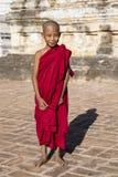 Bagan, Мьянма, 29-ое декабря 2017: Молодой буддийский послушник стоит с его красной робой перед пагодой Стоковые Изображения