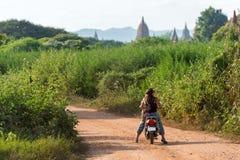 BAGAN, MYANMAR - 1 DE DICIEMBRE DE 2016: Mujer en una motocicleta en el fondo de un paisaje rural Copie el espacio para el texto Fotos de archivo libres de regalías