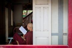 Bagan, Myanmar - 24 de julho de 2014: A monge burmese local está sentando-se perto foto de stock