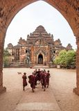 Group of Novice Monks happily entering Dhammayangyi Temple for morning prayers, Bagan, Myanmar royalty free stock photography
