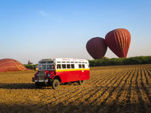 Bagan, Myanmar - January 26, 2015: Balloons Over Bagan vintage s. Huttle bus with dark red balloons, blue sky and pagoda background on dried field in the morning Stock Photos