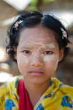 Bagan, Myanmar - January 25, 2014: Girl at small family snack ta. A girl wears traditional Thanaka on her face at her family's small snack shop on in Bagan Royalty Free Stock Photography
