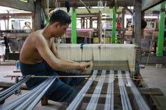 Bagan, Myanmar - 24. Juli 2014: Lokaler birmanischer Mann macht Stoff lizenzfreies stockbild