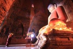 BAGAN MYANMAR - Maj 2016: Munkbränningen undersöker framme av Buddhastatyn inom pagod på Maj, 2016 i Bagan Royaltyfria Bilder
