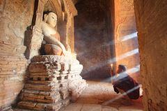 BAGAN MYANMAR - Maj 2016: Munkbränningen undersöker framme av Buddhastatyn inom pagod på Maj, 2016 i Bagan Arkivfoto