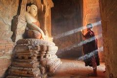 BAGAN, MYANMAR - mayo de 2016: Velas ardientes del monje delante de la estatua de Buda dentro de la pagoda en mayo de 2016 en Bag Imagen de archivo