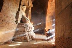 BAGAN, MYANMAR - mayo de 2016: Velas ardientes del monje delante de la estatua de Buda dentro de la pagoda en mayo de 2016 en Bag Fotos de archivo
