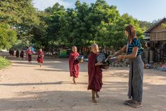 Young buddhist novices walk to collect alms and offerings on the streets of Bagan, Myanmar. Bagan, Myanmar - October 13, 2016: Young buddhist novices walk to stock image
