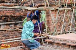 BAGAN MYANMAR SEPTEMBER 12, 2016: Burmese folk som bygger ett material till byggnadsställning med bambu för de skadade templen ef Royaltyfria Bilder