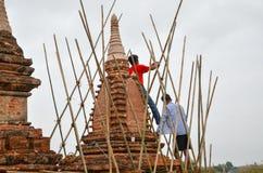 BAGAN MYANMAR SEPTEMBER 12, 2016: Burmese folk som bygger ett material till byggnadsställning med bambu för de skadade templen ef Arkivbild