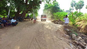 Bagan road, Myanmar. Car rides on the dusty rural road and passes road workers at Bagan Archaeological Zone in Myanmar stock video footage