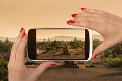 Bagan snapshot. Bagan snapshot on smartphone screen in female hands with red nails. Female travel, vagabonding and backpacking Stock Photography
