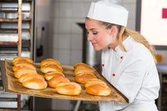 Bagare eller lärling i bageri som luktar nytt bröd och bullar Royaltyfri Bild