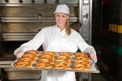 Bagare framme av ugnen med kringlor inom ett bageri Royaltyfri Foto