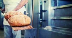 Bagare i bageri med bröd på skyffeln royaltyfria bilder
