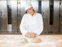 Bagare i bakehouse eller bageri som knådar deg Arkivfoto
