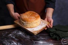 Bagare i förklädeinnehavbräde med varmt nytt bakat bröd på satsen arkivfoton