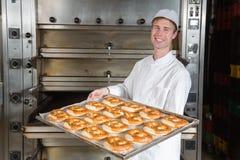 Bagare med bakningplattan mycket av bakelse i bageri arkivbild