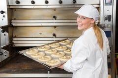 Bagare med bakningplattan mycket av kringlor Arkivfoto
