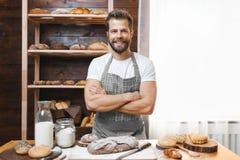 Bagare med en variation av läckert nytt bakat bröd och bakelse Arkivfoto