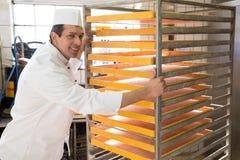Bagare med kuggen för bröd i ett bageri Fotografering för Bildbyråer