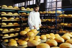 Bagare på bakgrunden av hyllor med bröd Arkivbilder