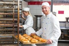 Bagare som framlägger magasinet med bakelse eller deg på bagerit Royaltyfria Foton