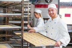 Bagare som framlägger magasinet med bakelse eller deg på bagerit Arkivfoto