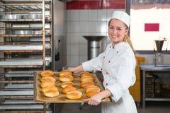 Bagare som framlägger magasinet med bakelse eller deg på bagerit fotografering för bildbyråer