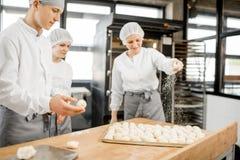 Bagare som gör bullar på tillverkningen arkivfoton