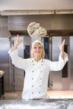 Bagare som kastar bröddeg i bageri eller bakehouse royaltyfria bilder