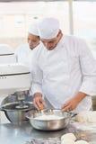 Bagare som knäcker ägget in i bunken Royaltyfria Foton