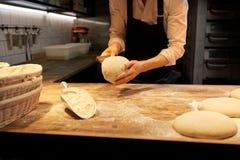Bagare som portion deg med bänkskäraren på bagerit Royaltyfri Bild