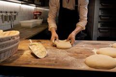 Bagare som portion deg med bänkskäraren på bagerit Arkivbilder