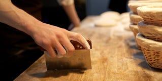 Bagare som portion deg med bänkskäraren på bagerit royaltyfria foton