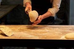 Bagare som portion deg med bänkskäraren på bagerit Arkivfoto