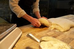 Bagare som portion deg med bänkskäraren på bagerit Arkivbild