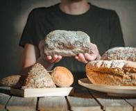 Bagare som rymmer nytt bröd i händer arkivbild