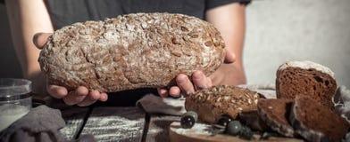 Bagare som rymmer nytt bröd i händer royaltyfri fotografi