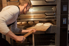 Bagare som sätter deg in i brödugnen på bagerit royaltyfria foton