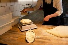 Bagare som väger bröddeg på skala på bagerit Royaltyfri Bild