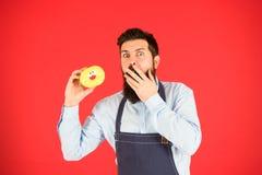 Bagarehållmunk Rolig hipster Skäggig mankock Kockman i kafé Banta och sund mat Den uppsökte mannen äter munken arkivfoto