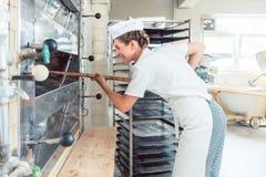 Bagarekvinna som får bröd ut ur bageriugnen arkivfoto